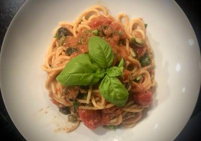 Spaghetti alla Puttanesca mit Basilikum serviert