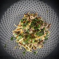 Pasta mit Wurstbrät und Gemüse serviert